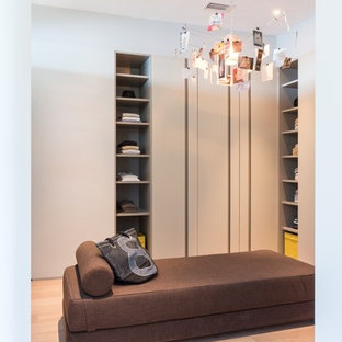 Design ideas for a large modern gender-neutral dressing room in Miami with open cabinets, light wood cabinets and bamboo floors.
