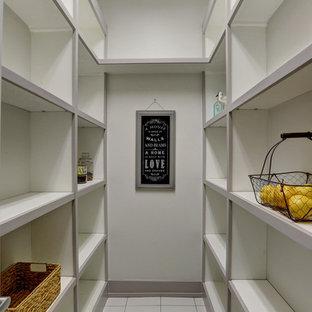 Diseño de armario vestidor marinero, de tamaño medio, con armarios abiertos, puertas de armario blancas, suelo de baldosas de porcelana y suelo blanco