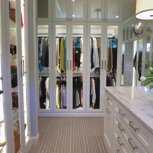 Esempio di un'ampia cabina armadio per donna con ante lisce, ante bianche e moquette