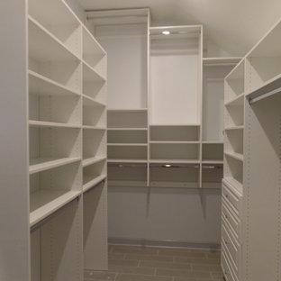 Diseño de armario vestidor unisex, actual, grande, con armarios con paneles con relieve, puertas de armario blancas, suelo de baldosas de porcelana y suelo gris