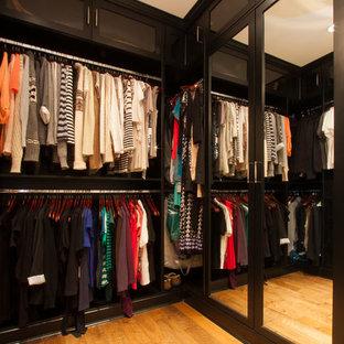 Modelo de armario vestidor unisex, tradicional, grande, con armarios con paneles lisos, puertas de armario de madera en tonos medios, suelo de madera clara y suelo marrón