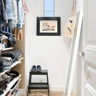 Modelo de armario vestidor unisex, nórdico, de tamaño medio, con armarios abiertos, puertas de armario blancas, suelo de madera clara y suelo beige