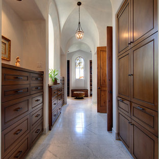 Example of a tuscan marble floor closet design in Austin with dark wood cabinets