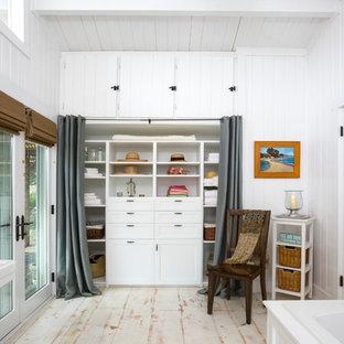 Cette photo montre un placard dressing bord de mer avec un placard avec porte à panneau encastré et un sol en bois peint.