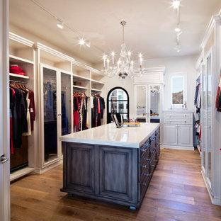 Ejemplo de armario vestidor de mujer, clásico renovado, grande, con armarios con paneles con relieve, puertas de armario de madera oscura y suelo de madera en tonos medios