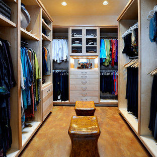 Design ideas for a large traditional women's dressing room in Dallas with flat-panel cabinets, light wood cabinets and concrete floors.
