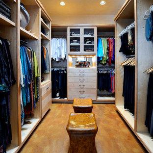 Diseño de vestidor de mujer, tradicional, grande, con armarios con paneles lisos, puertas de armario de madera clara y suelo de cemento