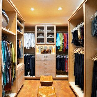 Foto de armario vestidor unisex, clásico renovado, grande, con armarios con paneles lisos, puertas de armario de madera clara y suelo de cemento