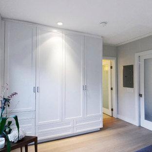Diseño de armario y vestidor unisex, costero, de tamaño medio, con armarios estilo shaker, puertas de armario blancas, suelo de madera clara y suelo beige