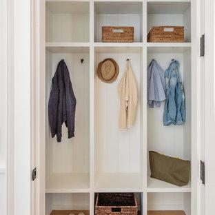Esempio di una cabina armadio stile marinaro con pavimento beige