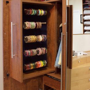 Ispirazione per una cabina armadio per donna design di medie dimensioni con ante lisce, ante in legno scuro e parquet chiaro