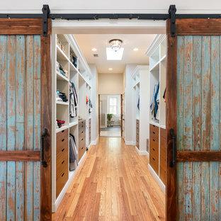 Ejemplo de armario vestidor unisex, costero, grande, con armarios con paneles lisos, puertas de armario de madera oscura, suelo de madera en tonos medios y suelo marrón