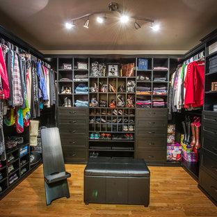 Imagen de armario vestidor unisex, tradicional renovado, grande, con armarios estilo shaker, puertas de armario negras y suelo de madera clara