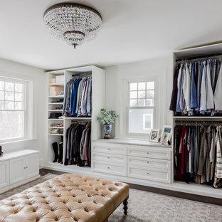 Klassisk inredning av ett walk-in-closet för kvinnor, med öppna hyllor, vita skåp, mörkt trägolv och brunt golv