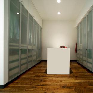 Ejemplo de armario vestidor moderno con suelo de madera en tonos medios y armarios con paneles lisos