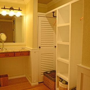 Diseño de vestidor unisex, tradicional, de tamaño medio, con armarios abiertos, puertas de armario blancas y suelo de bambú