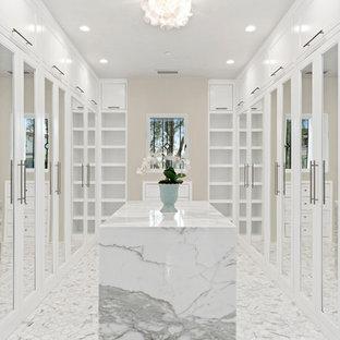 Cette image montre un dressing design avec un placard avec porte à panneau encastré, des portes de placard blanches et un sol blanc.