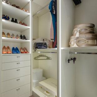Großer, Neutraler Eklektischer Begehbarer Kleiderschrank mit Glasfronten, weißen Schränken, braunem Holzboden und beigem Boden in Sonstige