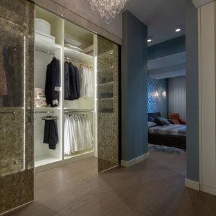 Ejemplo de armario vestidor unisex, ecléctico, grande, con armarios tipo vitrina, puertas de armario blancas, suelo de madera en tonos medios y suelo beige