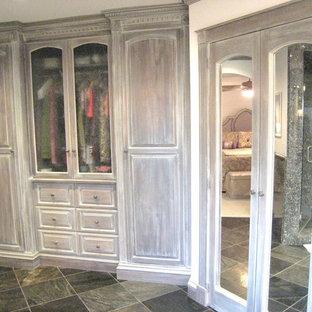 Ejemplo de armario vestidor unisex, clásico, grande, con armarios con paneles con relieve, puertas de armario con efecto envejecido y suelo de pizarra