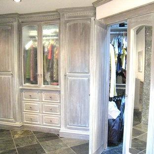 Idee per una grande cabina armadio unisex classica con ante con bugna sagomata, ante con finitura invecchiata e pavimento in ardesia