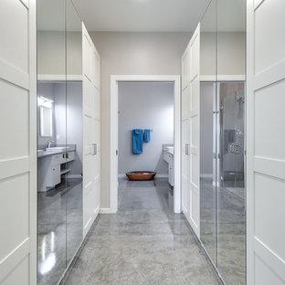 Esempio di una cabina armadio unisex moderna di medie dimensioni con ante in stile shaker, ante bianche, pavimento in cemento e pavimento grigio