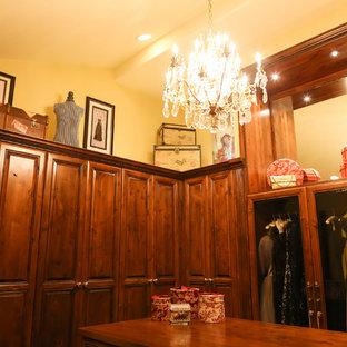 フェニックスの広い女性用ヴィクトリアン調のおしゃれなウォークインクローゼット (レイズドパネル扉のキャビネット、カーペット敷き、濃色木目調キャビネット) の写真