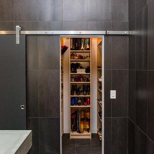 Imagen de vestidor de mujer, moderno, de tamaño medio, con armarios abiertos, puertas de armario de madera clara, suelo de baldosas de porcelana y suelo negro