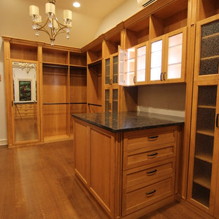 This is an example of a large traditional walk-in wardrobe in Other with glass-front cabinets and medium wood cabinets.