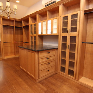 Photo of a large traditional walk-in wardrobe in Other with glass-front cabinets and medium wood cabinets.