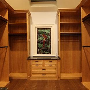 Ejemplo de armario vestidor tradicional, grande, con armarios tipo vitrina y puertas de armario de madera oscura