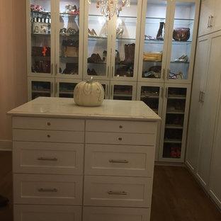 Imagen de armario vestidor de mujer, romántico, grande, con armarios estilo shaker, puertas de armario blancas y suelo marrón