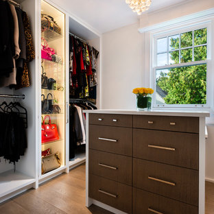 This is an example of a large asian women's dressing room in Vancouver with flat-panel cabinets, medium wood cabinets, light hardwood floors and brown floor.