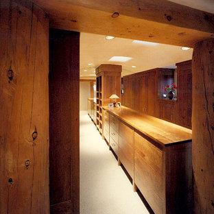 アルバカーキの中サイズの男女兼用サンタフェスタイルのおしゃれなウォークインクローゼット (フラットパネル扉のキャビネット、中間色木目調キャビネット、カーペット敷き) の写真