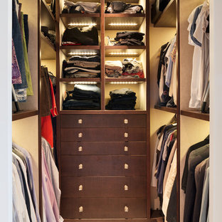Photo of a medium sized contemporary gender neutral walk-in wardrobe in London with open cabinets, dark wood cabinets, carpet and beige floors.