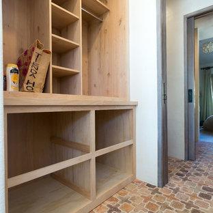 Lantlig inredning av ett walk-in-closet för könsneutrala, med skåp i ljust trä och klinkergolv i terrakotta