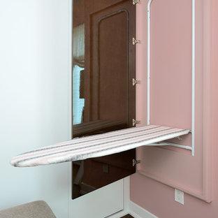 Diseño de vestidor de mujer, minimalista, grande, con armarios con paneles lisos, puertas de armario blancas y suelo de madera oscura