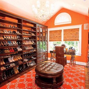 Foto di un grande spazio per vestirsi per donna eclettico con ante di vetro, ante in legno scuro, pavimento in legno massello medio e pavimento marrone