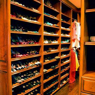 Diseño de armario vestidor de mujer, tradicional, grande, con puertas de armario de madera oscura, suelo de madera en tonos medios y armarios abiertos