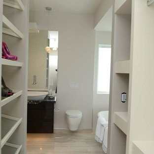 Large modern wardrobe in Other with flat-panel cabinets, dark wood cabinets and travertine flooring.
