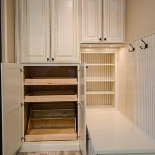 Modelo de armario vestidor unisex, clásico, de tamaño medio, con armarios con paneles con relieve, puertas de armario con efecto envejecido y suelo de baldosas de porcelana