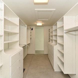 Foto de armario vestidor unisex, moderno, de tamaño medio, con armarios con paneles lisos, puertas de armario blancas, suelo de cemento y suelo gris
