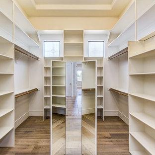 Ejemplo de vestidor clásico renovado, grande, con armarios abiertos, puertas de armario blancas, suelo de madera oscura y suelo marrón