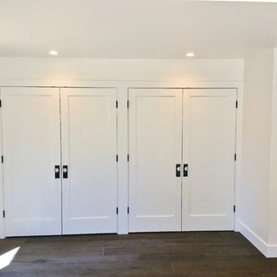 This is an example of a mid-sized midcentury built-in wardrobe in San Francisco with shaker cabinets, white cabinets, dark hardwood floors and brown floor.