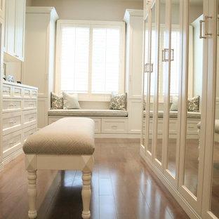 Ejemplo de vestidor unisex, tradicional renovado, grande, con puertas de armario blancas, suelo de madera en tonos medios, suelo marrón y armarios con paneles empotrados