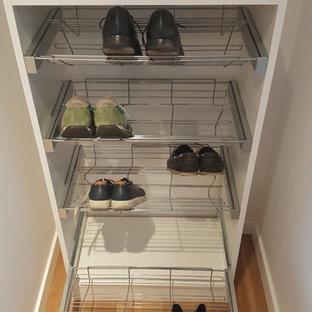 Imagen de armario unisex, moderno, pequeño, con armarios con paneles lisos, puertas de armario blancas, suelo laminado y suelo marrón
