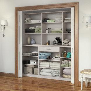 Foto de armario unisex, actual, pequeño, con armarios abiertos, puertas de armario blancas y suelo de madera en tonos medios