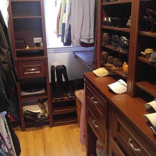 Diseño de armario vestidor de hombre, tradicional, pequeño, con armarios con paneles con relieve, puertas de armario marrones, suelo de madera clara y suelo marrón