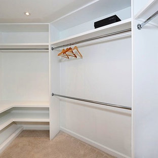 Mid-sized coastal gender-neutral carpeted and beige floor walk-in closet photo in Orange County with flat-panel cabinets and white cabinets