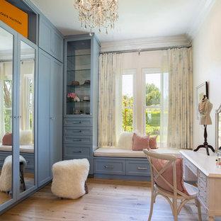 Aménagement d'un dressing room classique pour une femme avec un placard à porte shaker, des portes de placard bleues, un sol en bois brun et un sol marron.